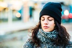 Adolescente hermoso triste gritador con el sombrero negro y la capa gris, los ojos cerrados - entrene al fondo Imagen de archivo libre de regalías
