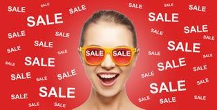 Adolescente heureuse aux nuances avec des signes de vente Images stock