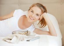 Adolescente heureuse avec le distant et le maïs éclaté de TV Photo libre de droits