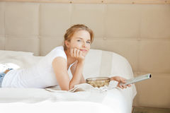 Adolescente heureuse avec le distant et le maïs éclaté de TV Image stock