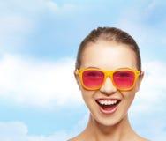 Adolescente heureuse dans des lunettes de soleil roses Image libre de droits