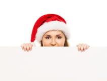Adolescente heureuse dans un chapeau de Noël tenant une grande bannière Photos libres de droits