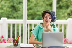 Adolescente heureuse effectuant son travail d'école à la maison Image libre de droits