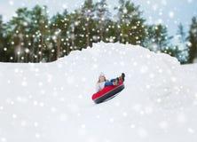 Adolescente heureuse glissant vers le bas sur le tube de neige Photo stock