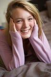 Adolescente heureuse s'asseyant dans la chambre à coucher image stock