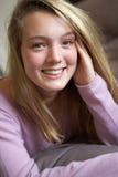 Adolescente heureuse s'asseyant dans la chambre à coucher image libre de droits