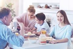 Adolescente heureuse souriant pour l'appareil-photo pendant le petit déjeuner de famille Photographie stock libre de droits