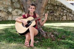 Adolescente hispánico bonito que toca una guitarra acústica Imagenes de archivo