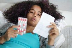 Adolescente hispánico en la cama en casa que toma la píldora para el frío Imagen de archivo libre de regalías