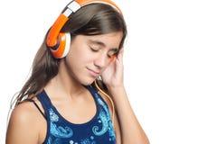 Adolescente hispánico hermoso que disfruta de música en los auriculares anaranjados brillantes Fotografía de archivo libre de regalías