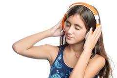 Adolescente hispánico hermoso que disfruta de música en los auriculares anaranjados brillantes Imagen de archivo libre de regalías