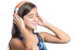 Adolescente hispánico hermoso que disfruta de música en los auriculares anaranjados brillantes Imagen de archivo