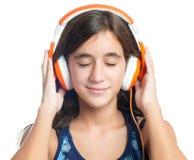 Adolescente hispánico hermoso que disfruta de música en los auriculares anaranjados brillantes Foto de archivo libre de regalías