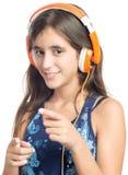 Adolescente hispánico hermoso que disfruta de música en los auriculares anaranjados brillantes Foto de archivo