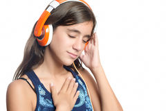 Adolescente hispánico hermoso que disfruta de música en los auriculares anaranjados brillantes Fotografía de archivo