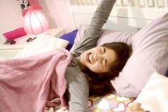 Adolescente hispánico lindo que bosteza apenas para despertar en su cama imagenes de archivo