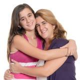 Adolescente hispánico que abraza a su madre aislada en blanco Foto de archivo