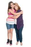 Adolescente hispánico que abraza a su madre aislada en blanco Fotos de archivo