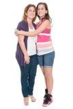 Adolescente hispánico que abraza a su madre aislada en blanco Foto de archivo libre de regalías