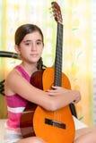 Adolescente hispánico que toca la guitarra en casa Foto de archivo