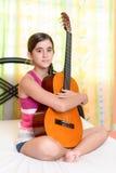 Adolescente hispánico que toca la guitarra en casa Foto de archivo libre de regalías