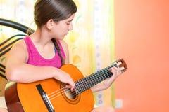 Adolescente hispánico que toca la guitarra en casa Imagen de archivo