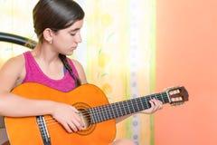 Adolescente hispánico que toca la guitarra en casa Imágenes de archivo libres de regalías
