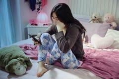 Adolescente hispánico triste que se sienta en la cama que mira el mensaje en el teléfono Imagen de archivo libre de regalías