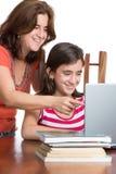 Adolescente hispánico y su madre que hojean el web y la risa Imágenes de archivo libres de regalías