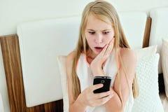 Adolescente impactante que miente en cama usando un teléfono móvil Imágenes de archivo libres de regalías