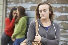 Adolescente infelice che è pettegolato circa dai pari fotografia stock