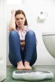 Adolescente infelice che esamina le bilancie pesa-persone Immagine Stock Libera da Diritti