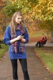 Adolescente infelice che si leva in piedi nella sosta di autunno Fotografie Stock