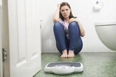 Adolescente infelice che si siede sul pavimento che esamina le bilancie pesa-persone Immagine Stock