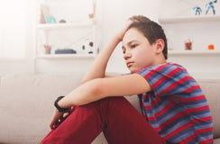 Adolescente infeliz aburrido que se sienta en casa Foto de archivo