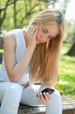 Adolescente infeliz con el teléfono móvil Foto de archivo libre de regalías