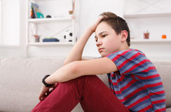 Adolescente infeliz furado que senta-se em casa imagem de stock royalty free
