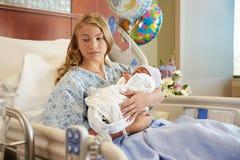 Adolescente infeliz que detiene al hijo recién nacido del bebé en hospital Foto de archivo libre de regalías