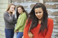 Adolescente infeliz que está sendo bisbilhotado aproximadamente por pares Foto de Stock Royalty Free