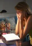 Adolescente infeliz que mira el diario en dormitorio la noche Imagen de archivo