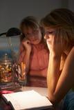 Adolescente infeliz que mira el diario en dormitorio la noche Fotos de archivo