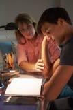 Adolescente infeliz que mira el diario en dormitorio la noche fotografía de archivo