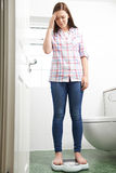 Adolescente infeliz que se coloca en básculas de baño Fotos de archivo libres de regalías