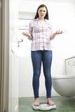 Adolescente infeliz que se coloca en básculas de baño Imagen de archivo libre de regalías