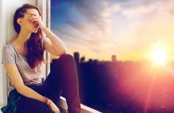 Adolescente infeliz que se sienta en alféizar Fotos de archivo