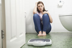 Adolescente infeliz que se sienta en el piso que mira básculas de baño Imagen de archivo