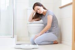 Adolescente infeliz que se sienta en el piso que mira básculas de baño Foto de archivo libre de regalías