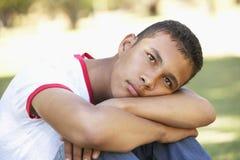 Adolescente infeliz que se sienta en parque Imagenes de archivo