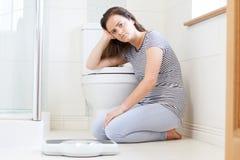 Adolescente infeliz que se sienta en piso con las básculas de baño Foto de archivo libre de regalías