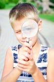 Adolescente inquisitivo con una lente en el parque Imagenes de archivo